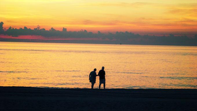 ビーチを歩く老夫婦